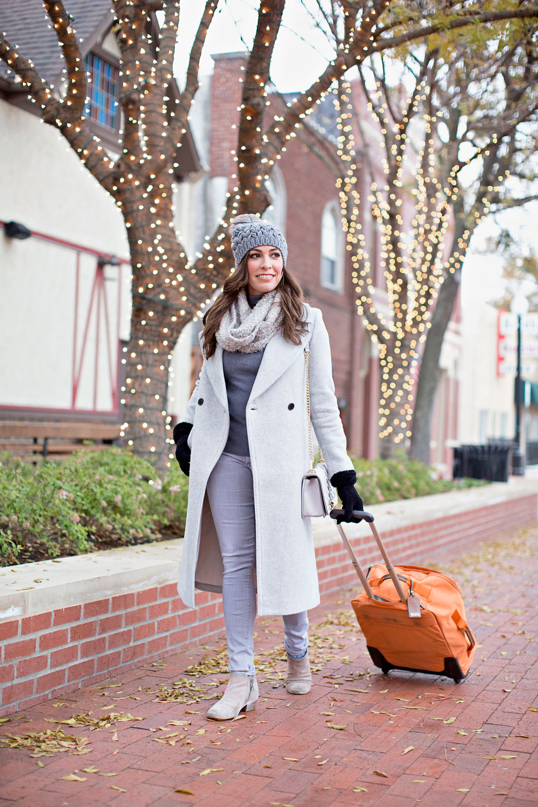 A Glam Lifestyle blogger shares easy travel outfits like a grey monochrome look including Club Monaco Daylina coat and grey Citizens of Humanity jeans