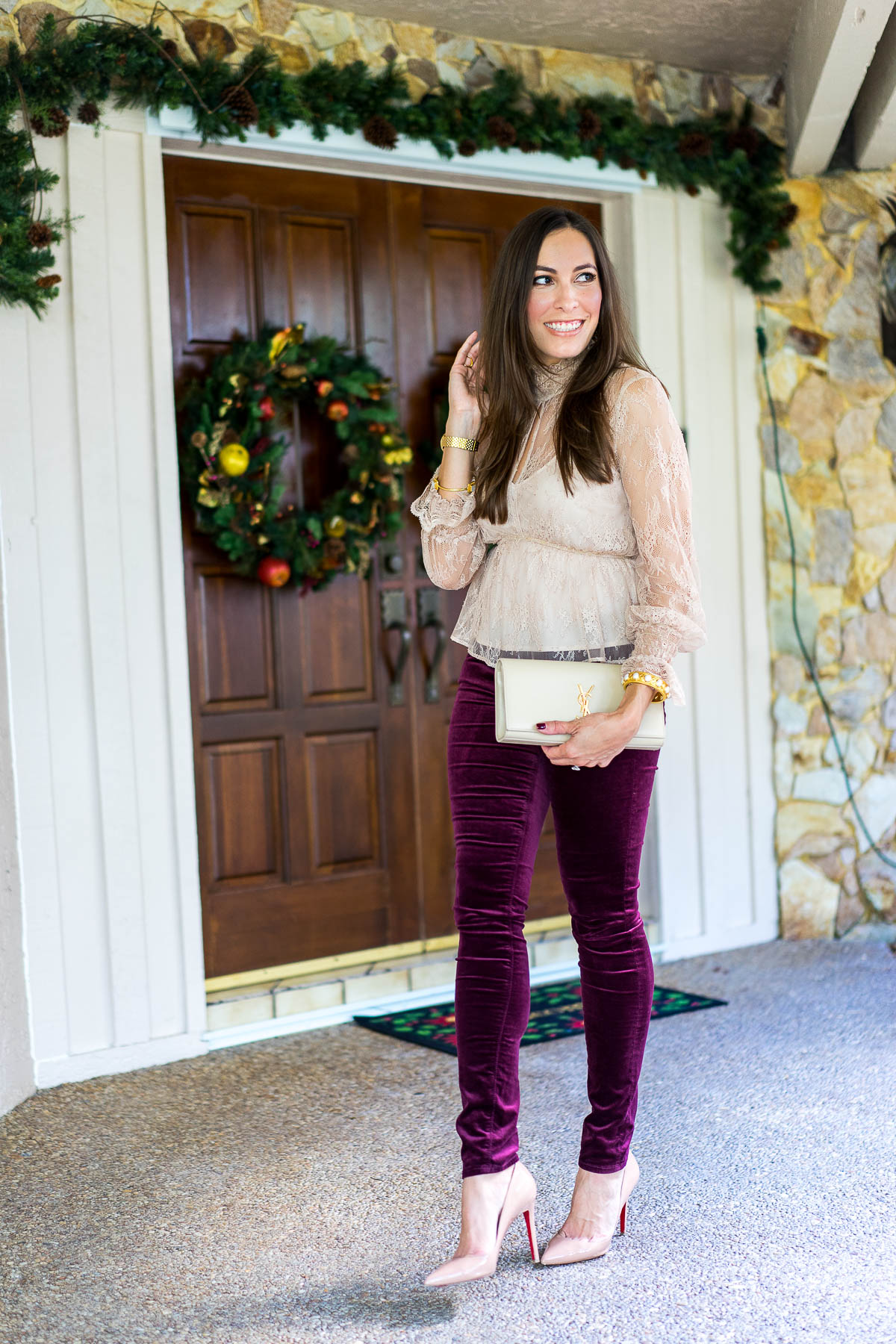 A Glam Lifestyle blogger Amanda shares her Christmas outfit wearing Intermix Genevieve blush lace top and AG Jeans burgundy velvet leggings with Christian Louboutin nude Pigalle pumps carrying YSL monogram clutch