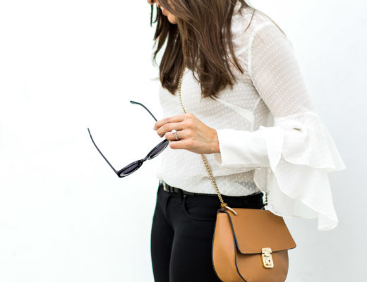 Fashion blogger Amanda who writes A Glam Lifestyle wears Olivia Palermo x Chelsea28 sheer white blouse with Chloe Drew bag dupe and black AG Jeans leggings