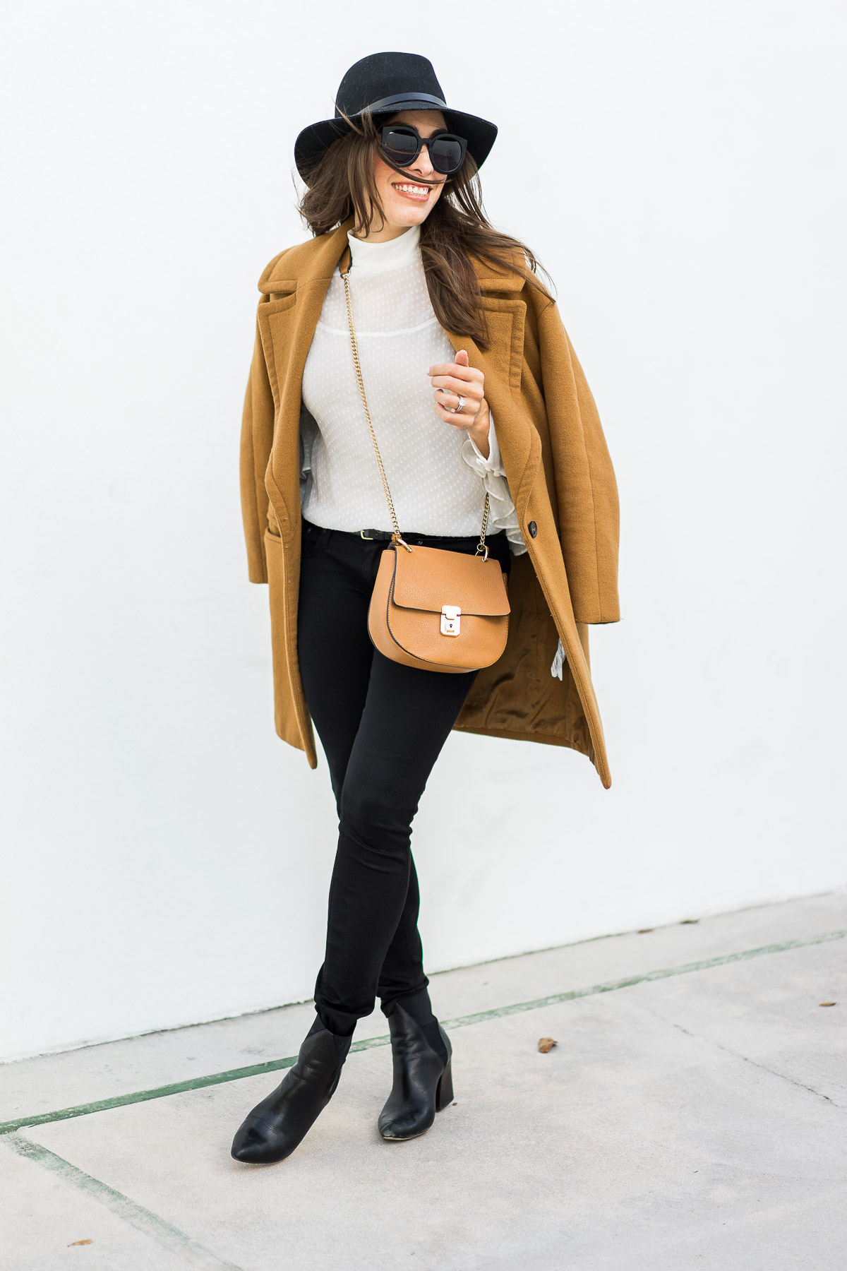Amanda from A Glam Lifestyle wears oversized lapel camel coat by Zara with sheer white blouse by Chelsea28 and Chloe Drew dupe bag