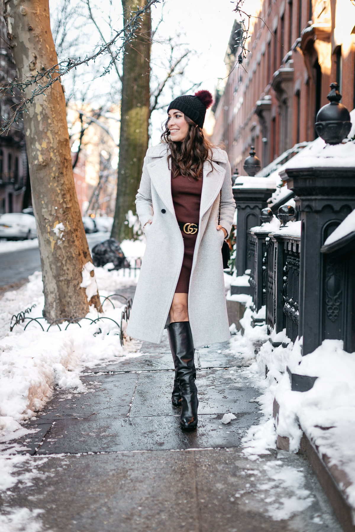 Amanda from A Glam Lifestyle blog wears 525 America burgundy sweater dress during NYFW Spring 2017 with MGemi Pendolo black boots and Club Monaco Daylina coat and Gucci double G belt for NYFW street style