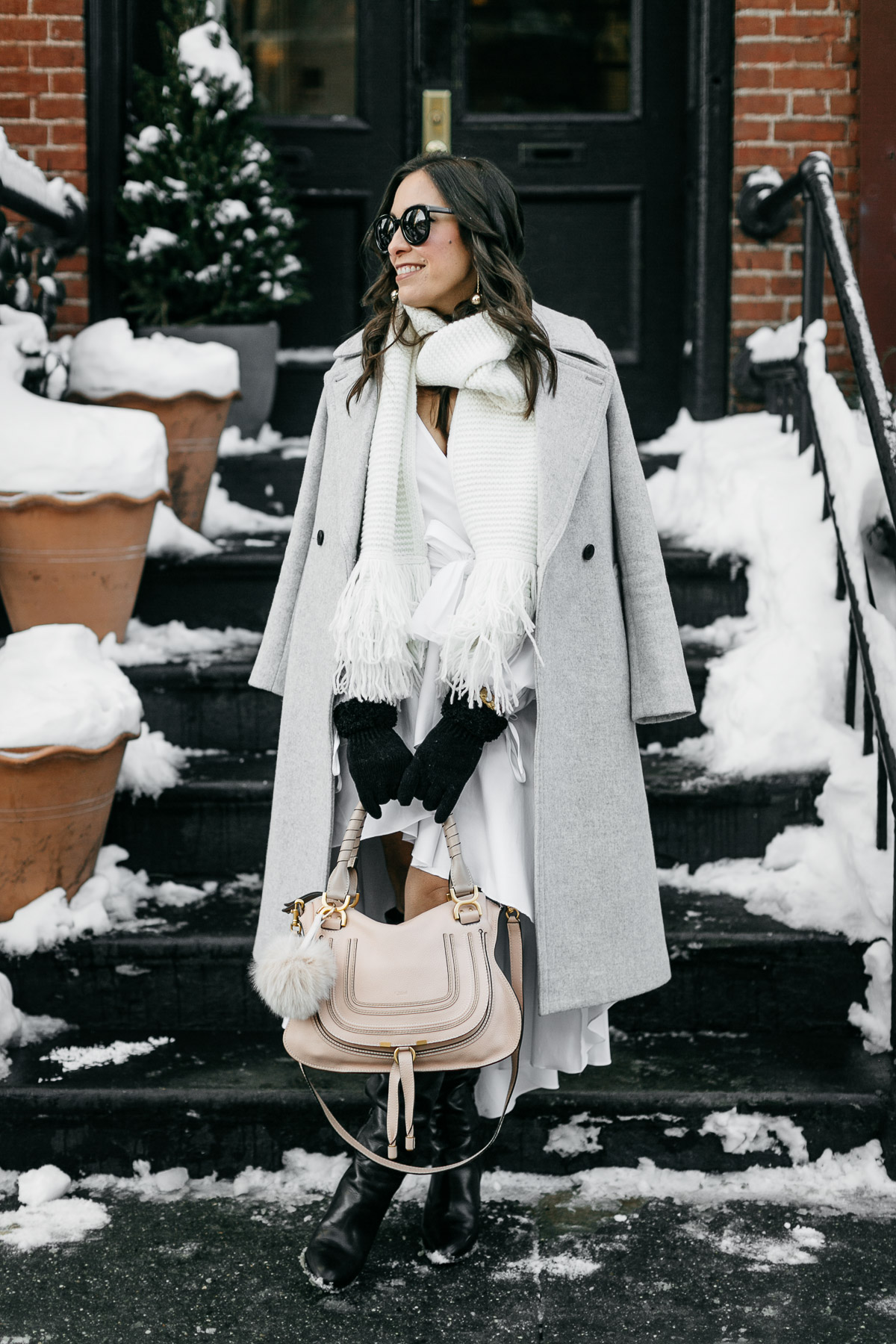 A Glam Lifestyle bloggers wears Carolina Constas high low white shirt dress for NYFW street style while carrying her Chloe Marcie bag and Club Monaco coat and white fringed scarf in Greenwich Village