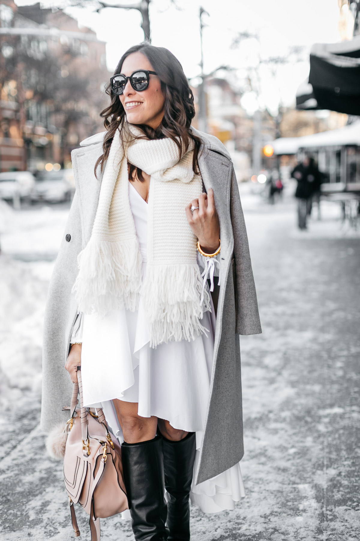 A Glam Lifestyle bloggers wears Carolina Constas Lena white shirt dress with MGemi Pendolo black boots and Club Monaco coat and Club Monaco Juki white fringed scarf to show her NYFW street style at NYFW Spring 2017 shows
