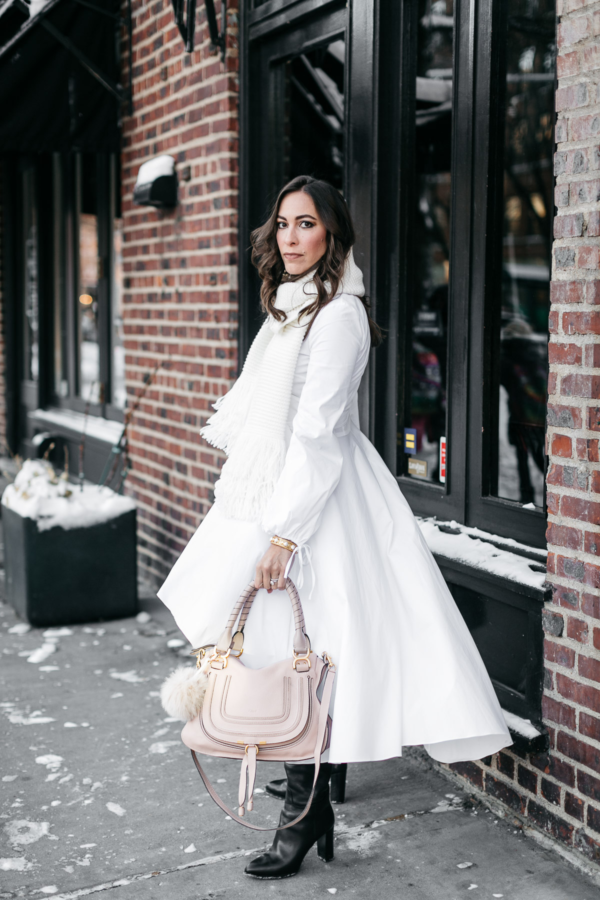 Amanda from A Glam Lifestyle blog wears Carolina Constas Lena white shirt dress during NYFW Spring 2017 shows carrying her Chloe Marcie bag and accessorized with MGemi Pendolo black boots and Club Monaco Juki white fringed scarf