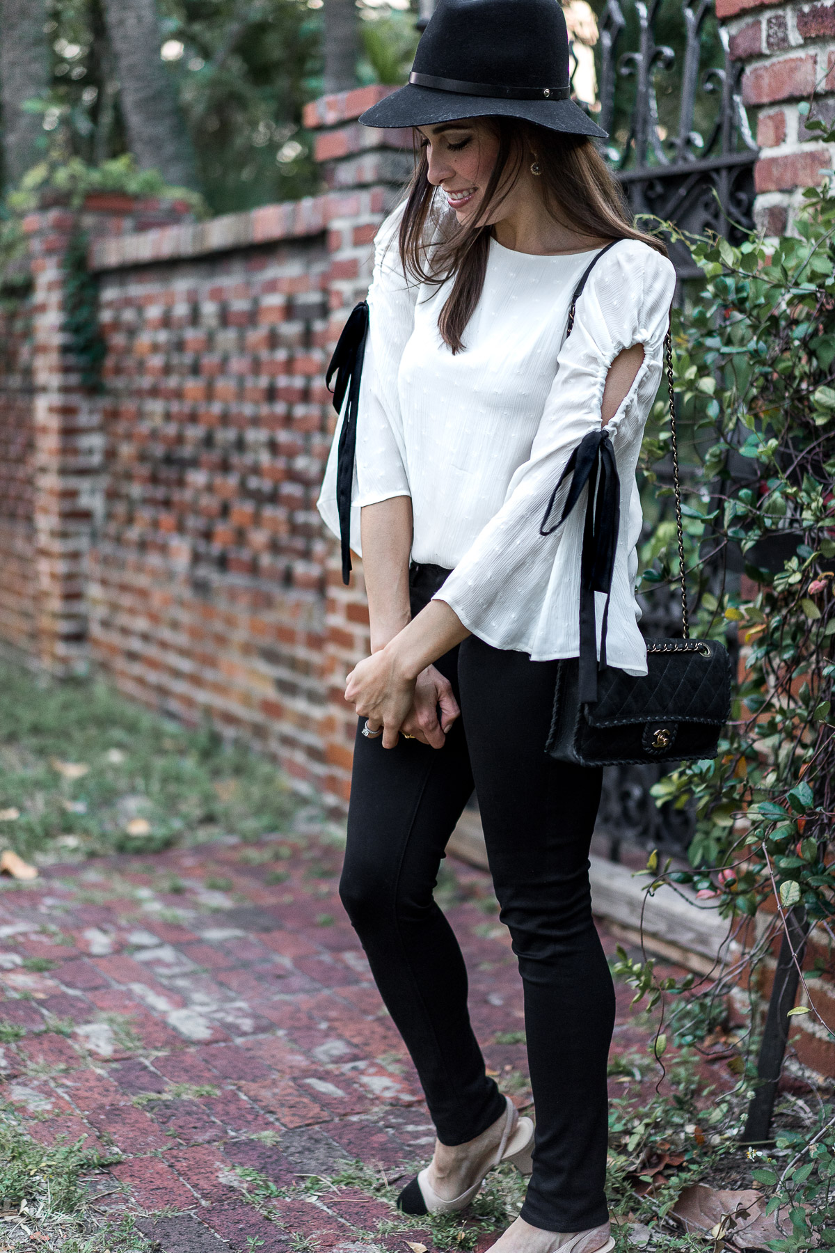 Pretty Club Monaco bell sleeve top with black ribbon tie styled by South Florida blogger Amanda of A Glam Lifestyle worn with Chanel suede bag and black AG Leggings jeans