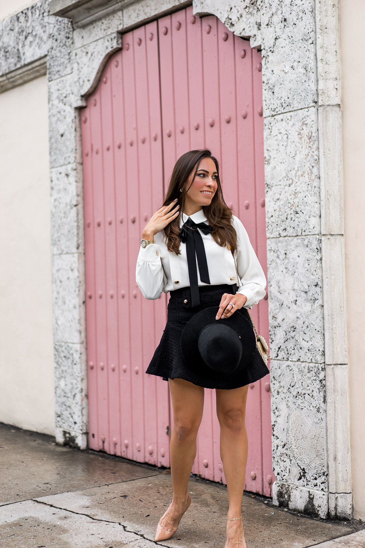 Storets melina tweed mini skirt is worn with bow tie blouse by Amanda of AGlamLifestyle blog at Fort Lauderdale pink door