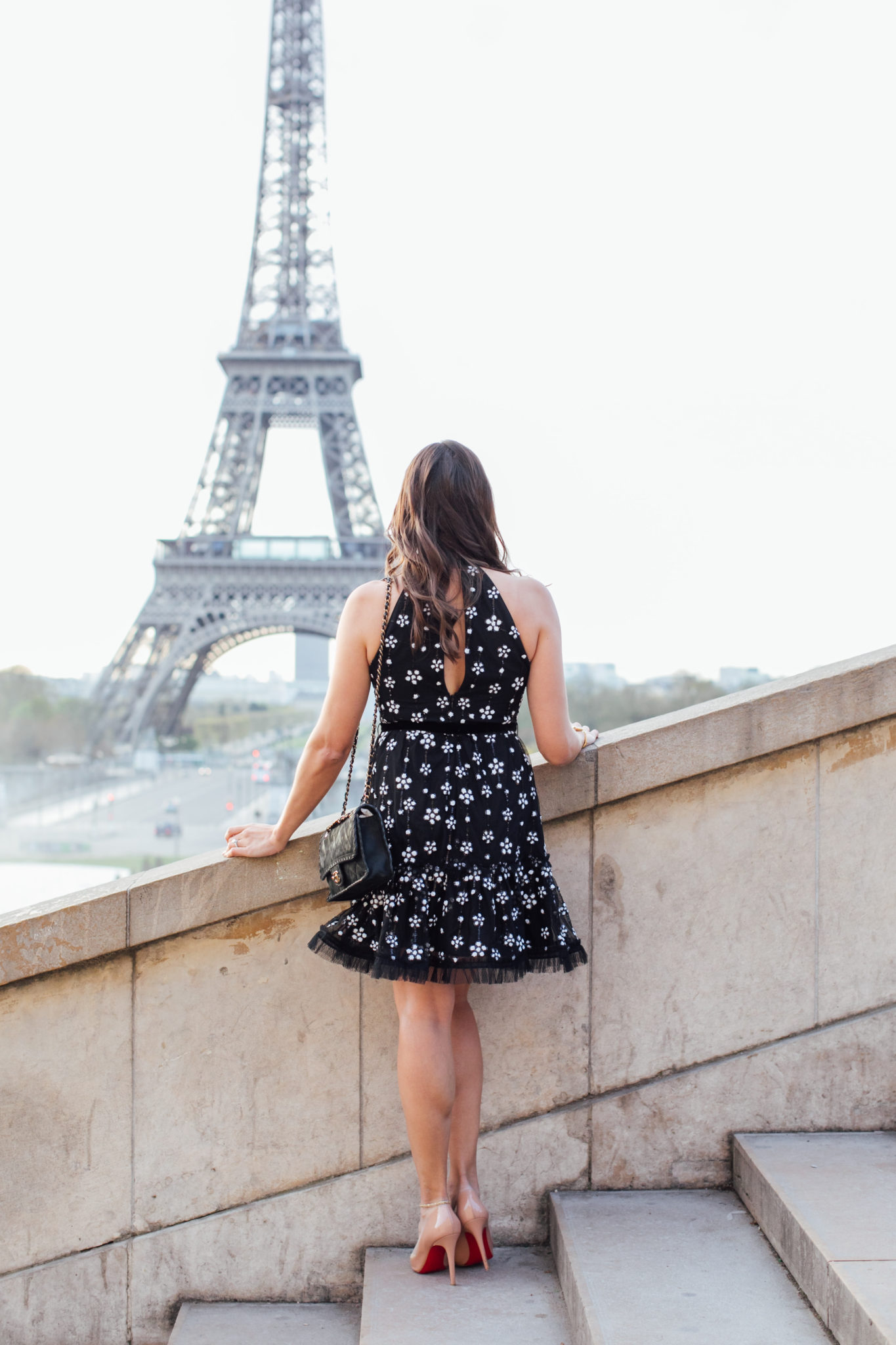 A Glam Lifestyle blogger Amanda shows her Paris fashion style at the Eiffel Tower in the Alexis Poppy dress with nude Christian Louboutin Pigalle pumps