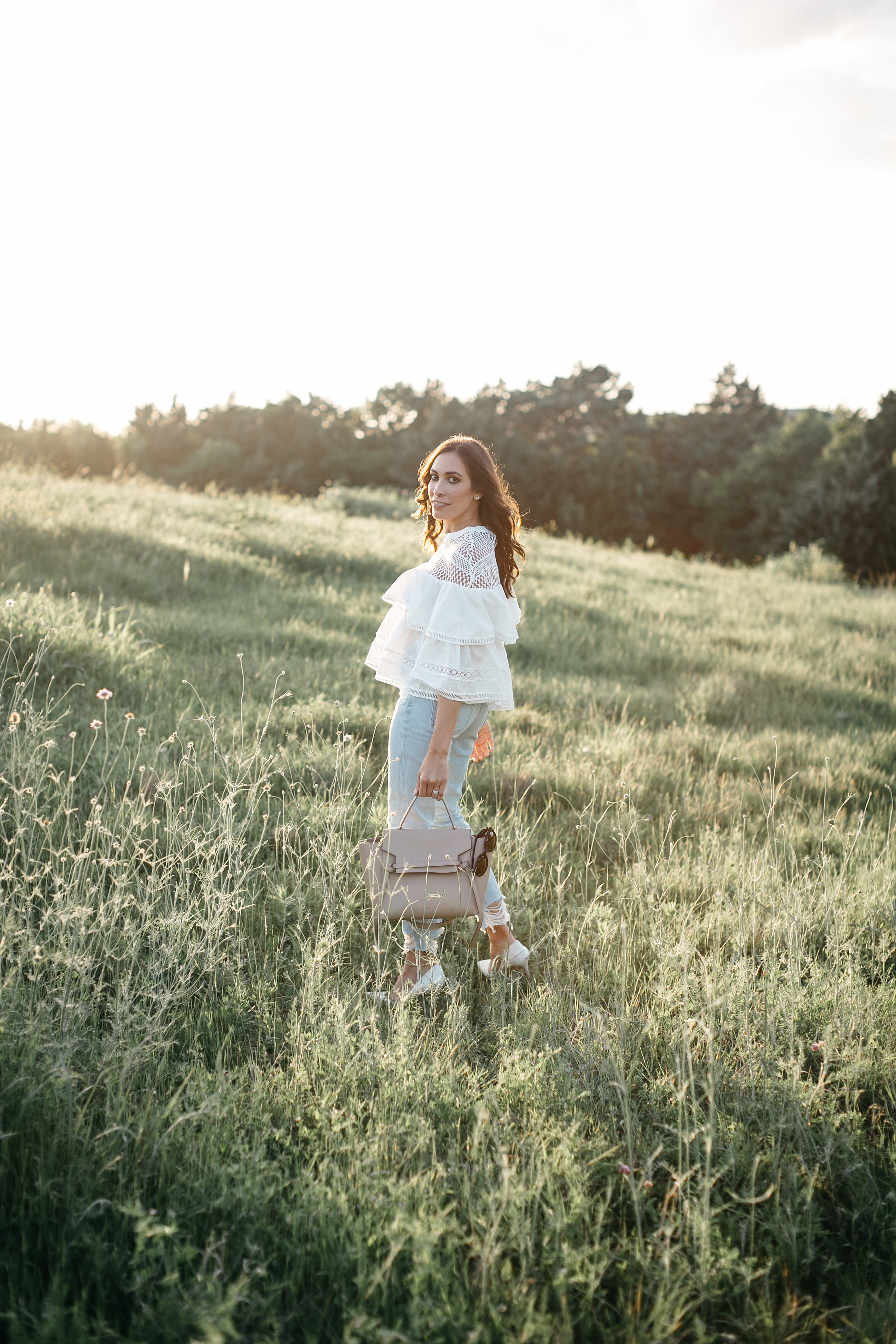 White tiered ruffle top styled by AGlamLifestyle blogger Amanda with Celine belt bag and Lovers and Friends distressed denim