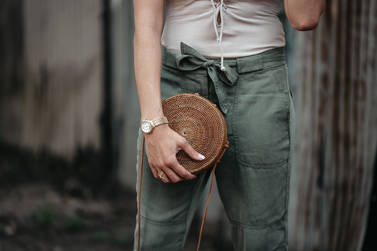 A round basket bag perfectly compliments tie waist cargo pants and a lace up bodysuit by Tularosa
