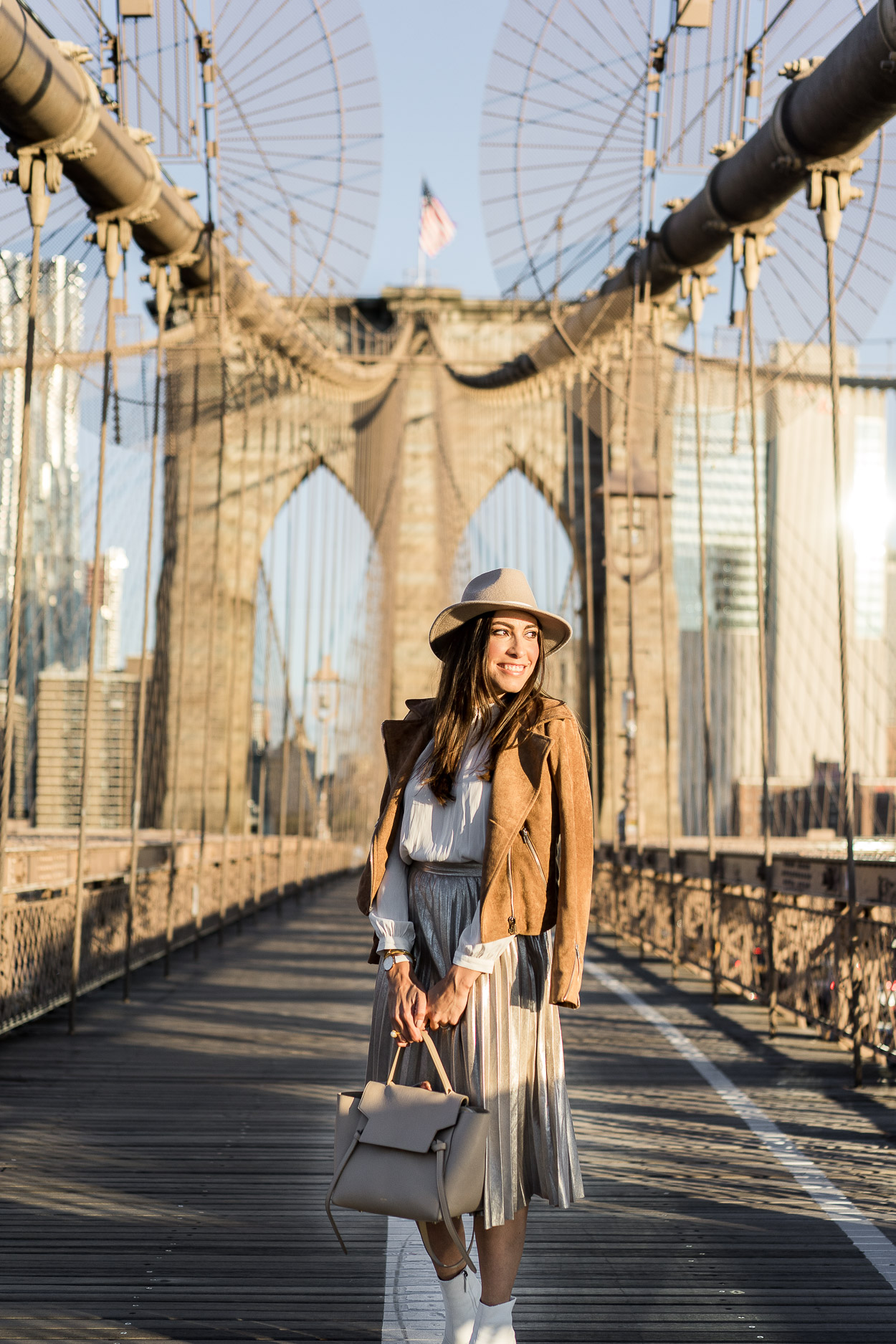 A metallic pleated skirt is a staple piece for Fall styled by Amanda of A Glam Lifestyle with her Celine belt bag, Topshop white booties and a Lulus camel suede jacket at the Brooklyn Bridge