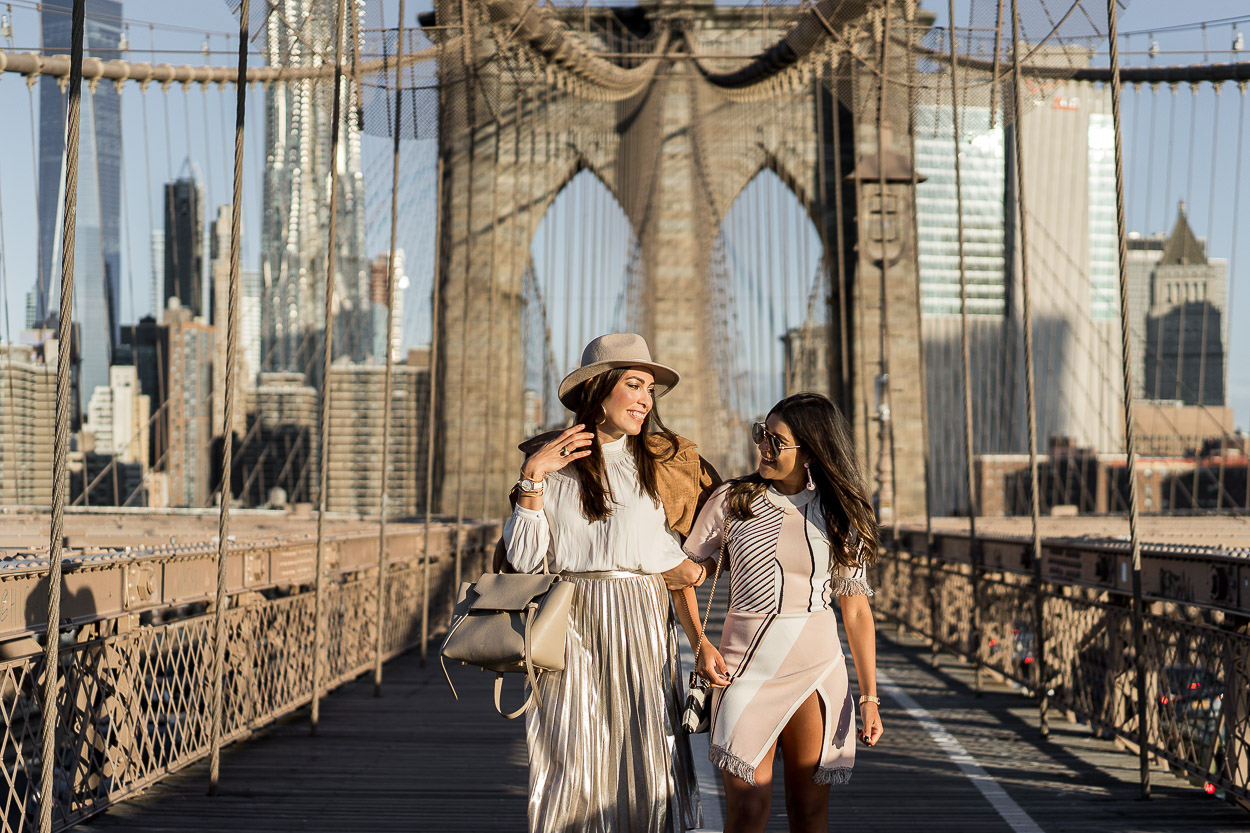 Amanda from A Glam Lifestyle blog styles a metallic pleated skirt with a cream blouse from Aritzia and her Celine belt bag during NYFW with fellow blogger Kelsey Kaplan Fashion