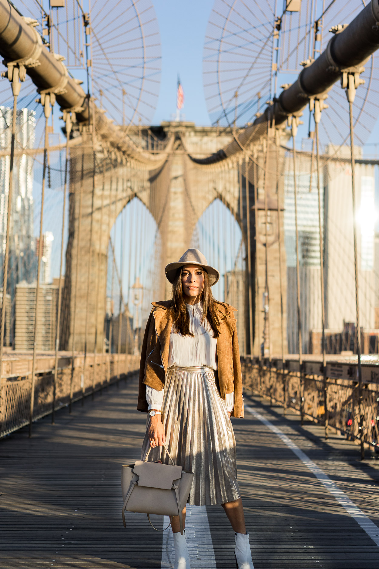 A metallic pleated skirt is trending for Fall and blogger A Glam Lifestyle shares how she styles hers with pretty neutrals like a cream top by Aritzia with a Lulus camel suede jacket and Topshop white ankle booties