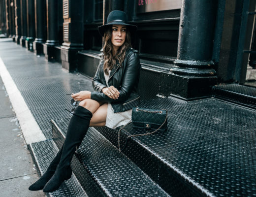 Amanda of A Glam Lifestyle blog wears Gentle Fawn Elijah faux wrap dress with Joie over the knee boots, Maje leather jacket, and Rag and Bone fedora to NYFW SS18 presentations