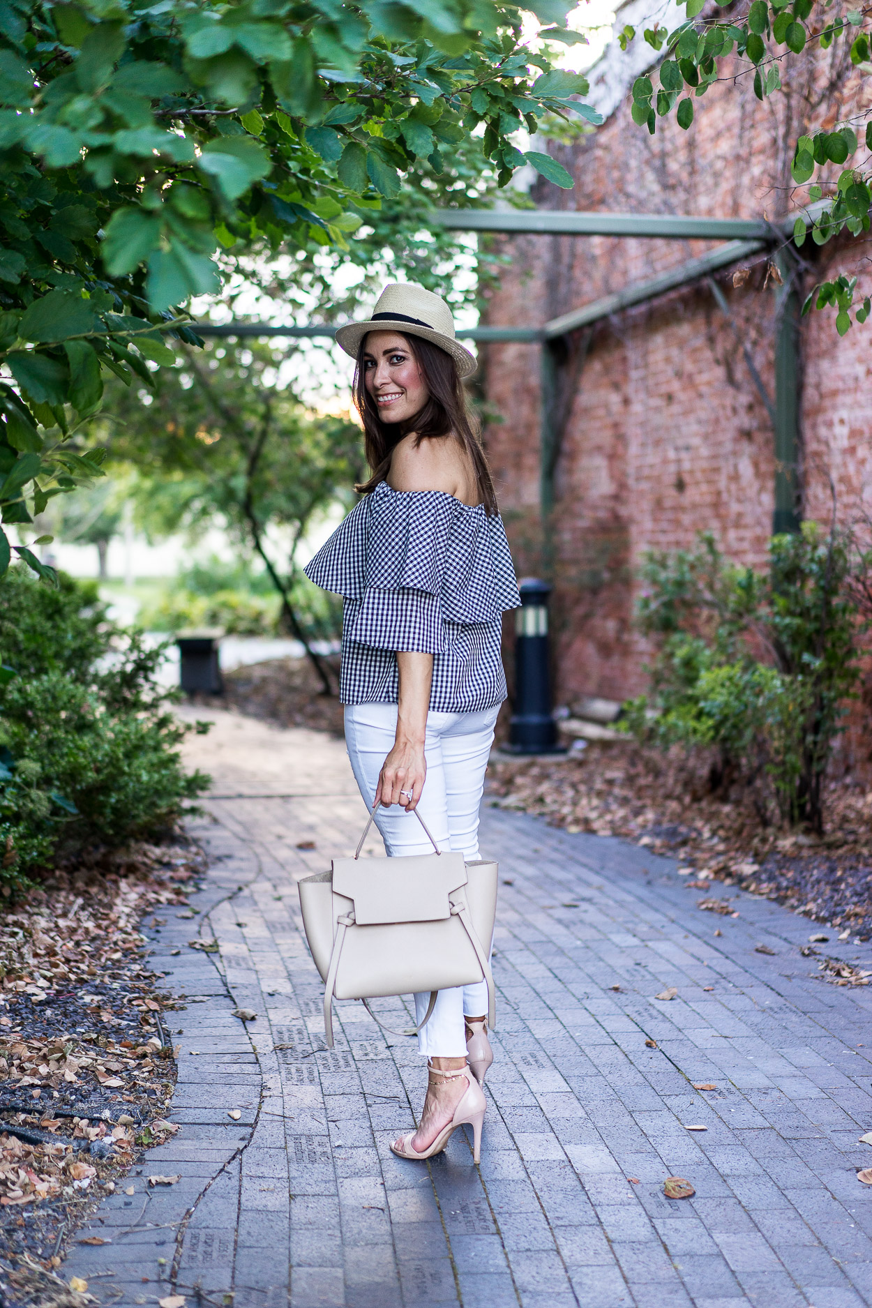 A Glam Lifestyle blogger wears Wayf gingham top with AG jeans white legging jeans and nude Steve Madden sandals and nude Celine Belt bag