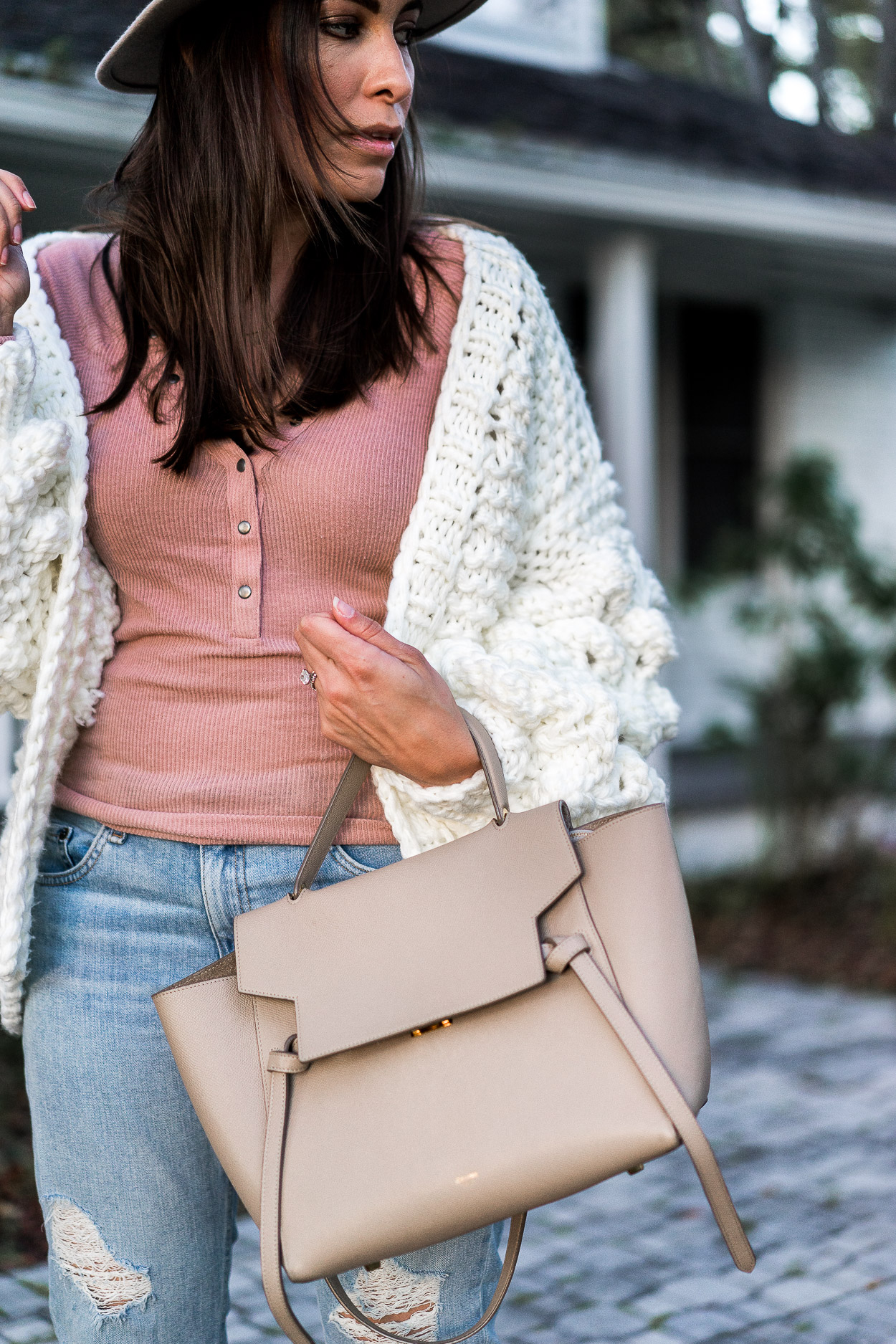 Amanda styles blush henley tee with white chunky sweater and carries her Celine belt bag